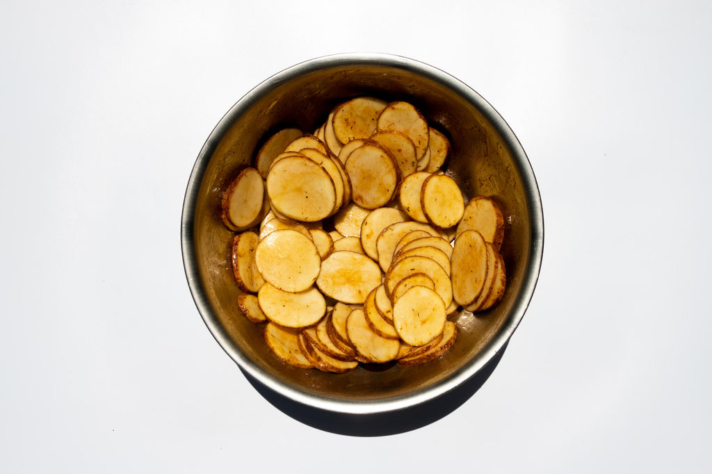 Sliced potatoes tossed with olive oil and seasoning
