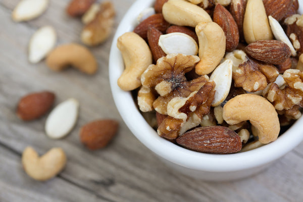Mixed nuts in a bowl on a wood table