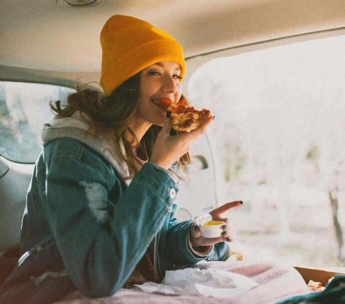Woman eating pizza in the car