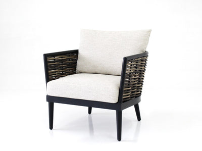 lounge chair in black powdercoated aluminium with handwoven synthetic rattan in natural two toned finishing, tapered legs and pale sand cushions and pillow