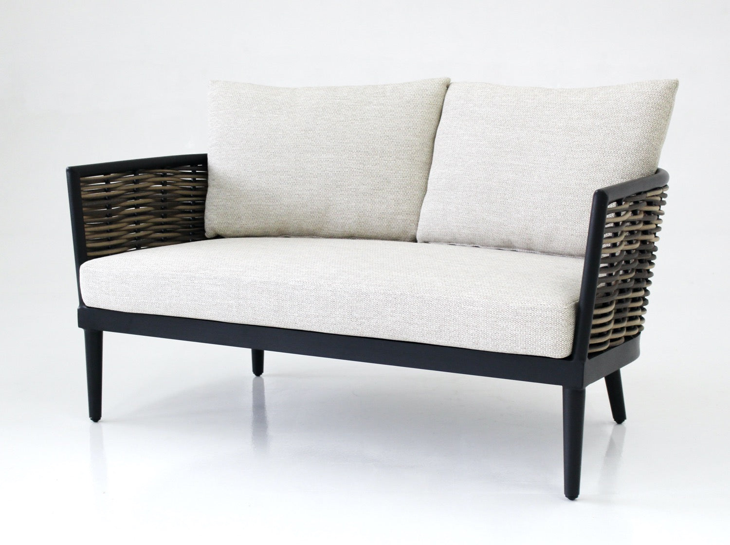 two seater sofa in black powdercoated aluminium with handwoven synthetic rattan in natural two toned finishing, tapered legs and pale sand cushions and pillow