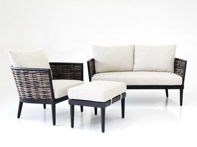 set of lounge chair, ottoman and sofa in black powdercoated aluminium with handwoven synthetic rattan in natural two toned finishing, tapered legs and pale sand cushions and pillow