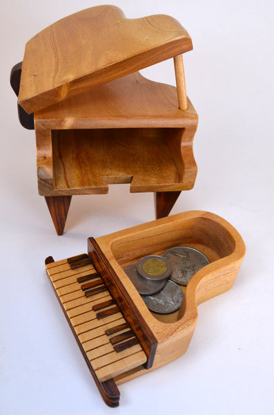puzzle box | handcrafted, wooden piano box, shown holding coins