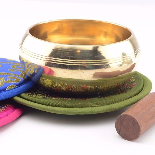 brass singing bowl shown with cushions and striker