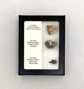 Three meteorites arranged vertically in a small black display box.  There is a white piece of paper on the left side of the box showing the composition and location of each of the meteorites.