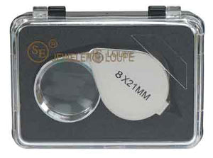 "A silver jeweler's loupe in a black case, with a clear plastic lid. The text ""8X21MM"" is visible in black print on the top of the loupe."