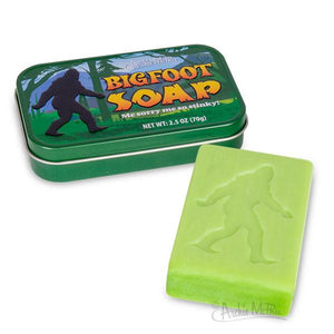 "To the left: a green tin reading ""Bigfoot Soap"" in yellow text. To the right: a light green bar of soap stamped with a silhouette of bigfoot."
