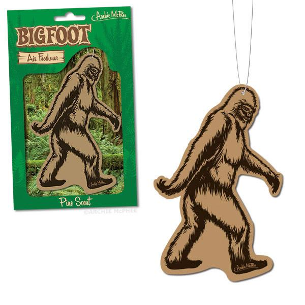 On the left, a bigfoot air freshener in it's green packaging. On the right, an unpackaged, brown bigfoot air freshener on a white string.