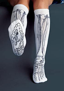 A person wearing white skeleton tube socks. Their right leg is extended towards the camera to show the pattern on the bottom of the socks.