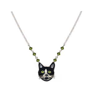 A black and white cloisonne cat on silver. The chain is silver and has green crystals.