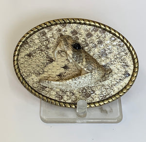 An oval belt buckle with the image of a rattlesnake head.