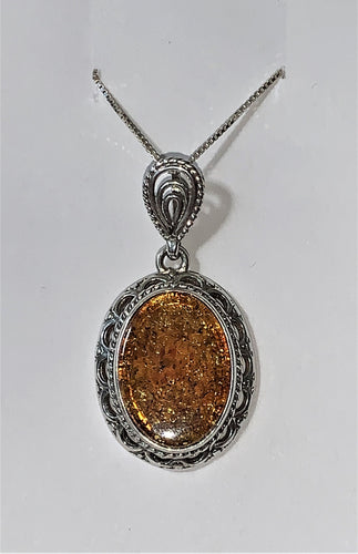 Large silver oval pendent with amber inlaid.