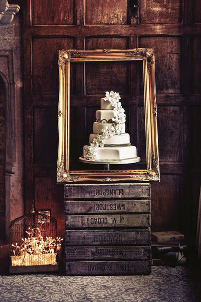 Frame your wedding cake literally by using a large wooden frame as a decoration