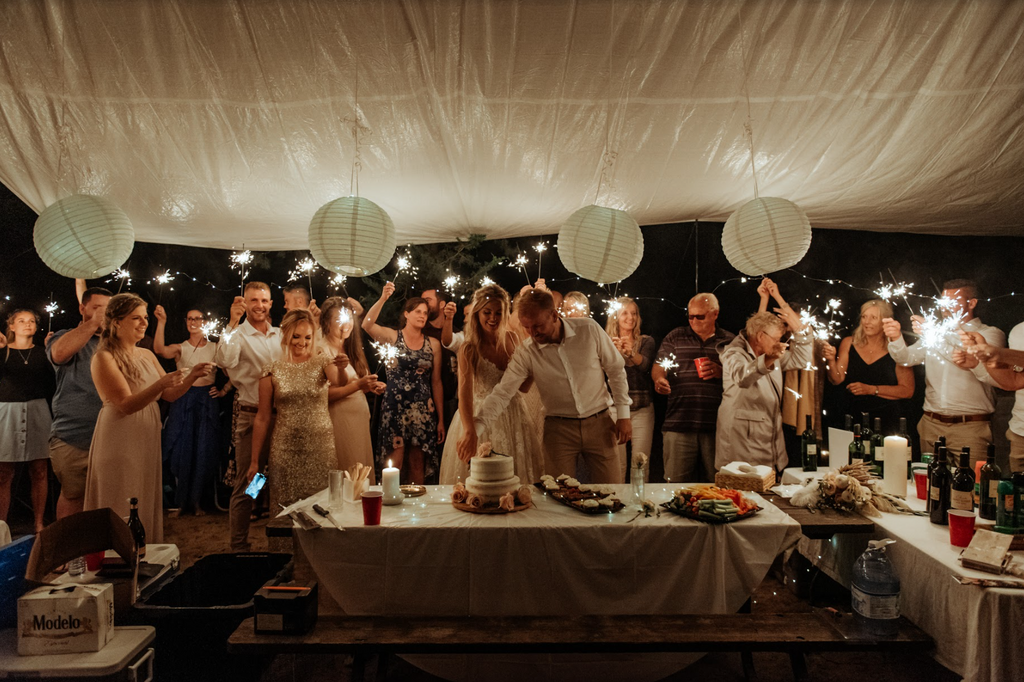Family and friends at a campground wedding under a tarp