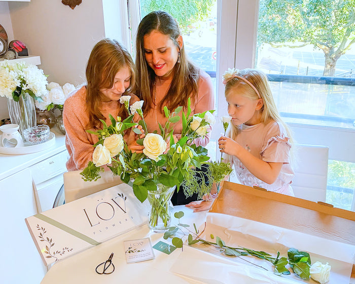 woman and children arranging flowers
