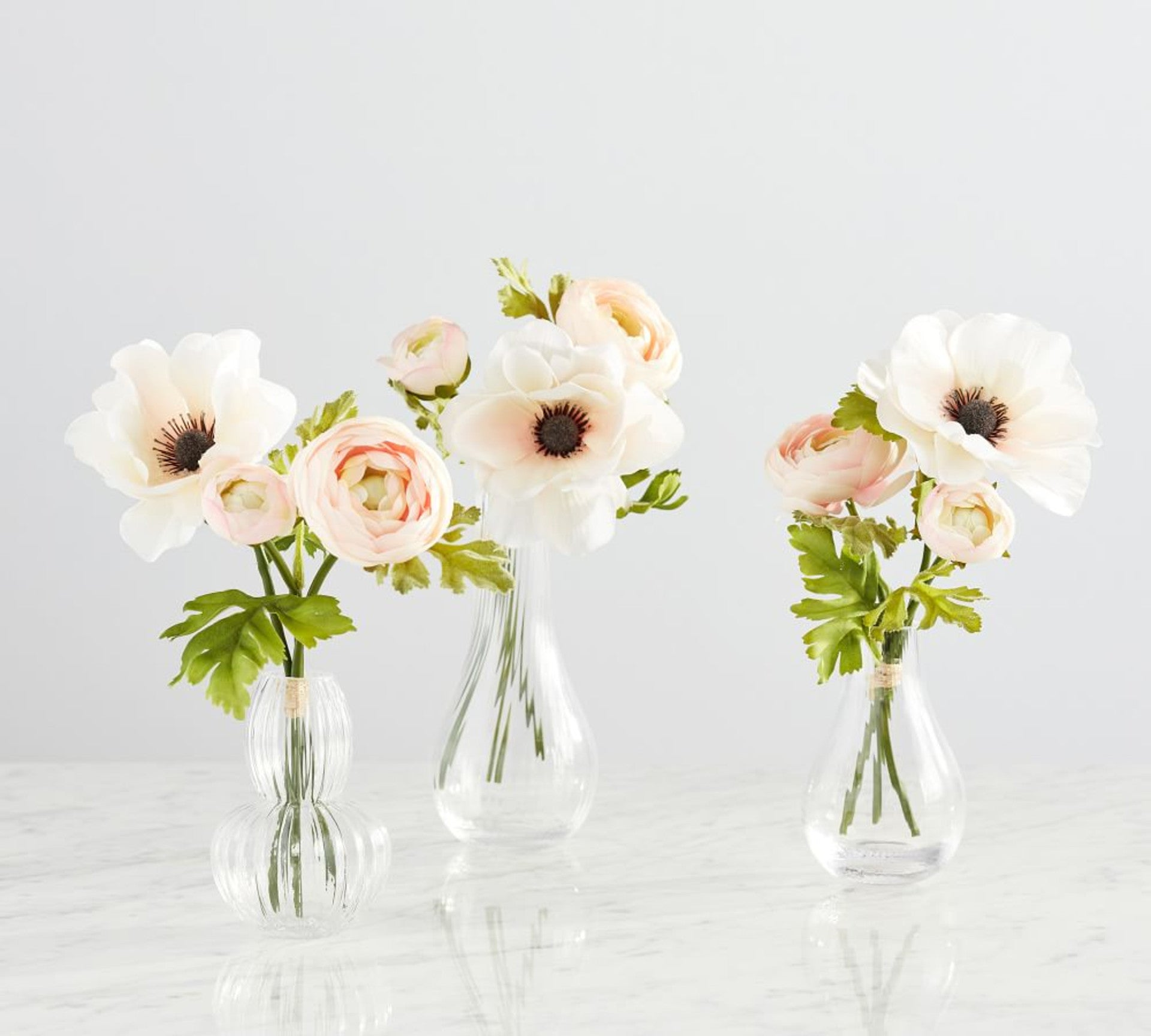 anemone and ranunculus in glass bud vases