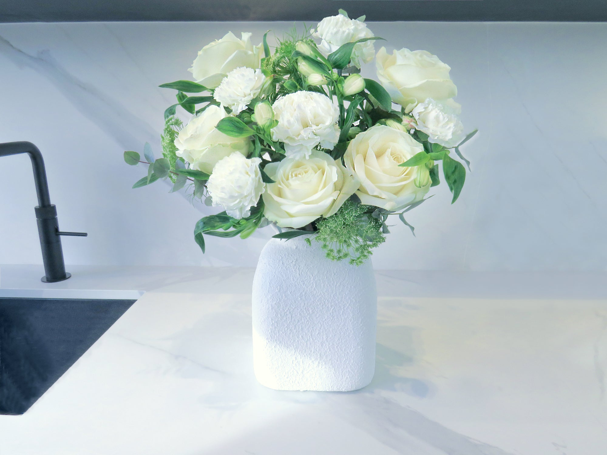 white flowers roses in kitchen in a white vase lov letterbox flowers