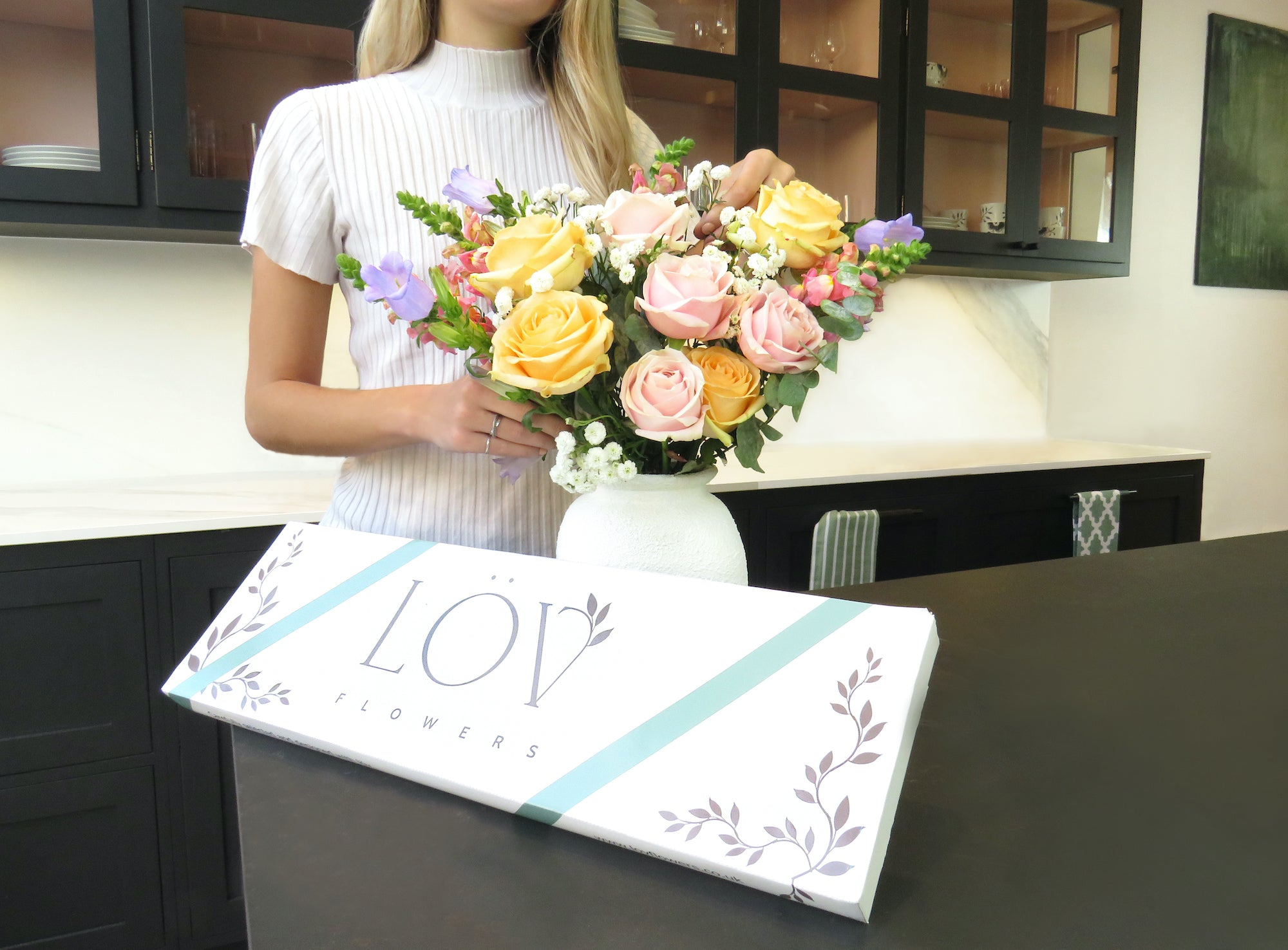 woman in kitchen arranging lov flowers letterbox flowers