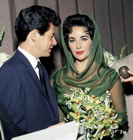 Eddie Fisher with Elizabeth Taylor who is wearing her diamond heart pendant during their wedding ceremony in Las Vegas on May 12, 1959