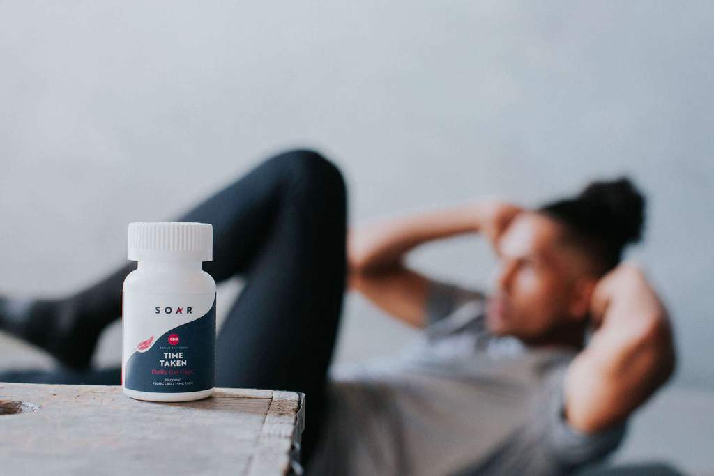 A bottle of SOAR™ CBD capsules in front of a man doing crunches