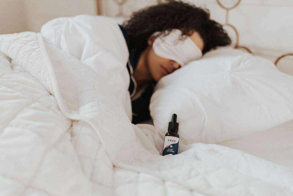 A woman sleeping next to a bottle of SOAR™ CBN tincture