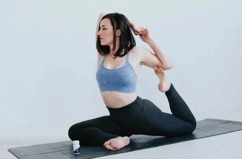 A woman using CBD for recovery while stretching