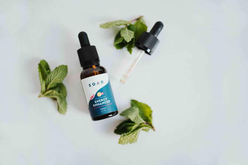A bottle of SOAR™ Energy Enhanced surrounded by mint leaves