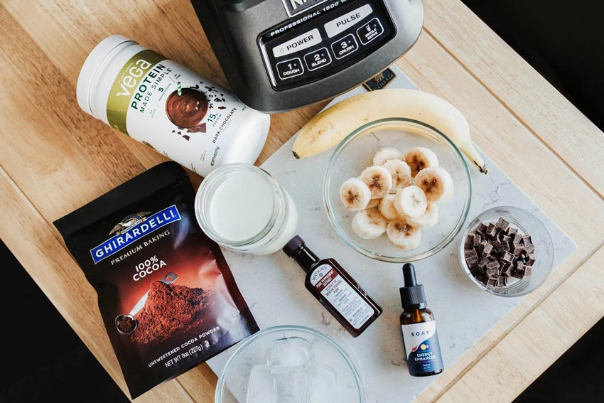 The ingredients for a chocolate peppermint protein shake laid out on a table