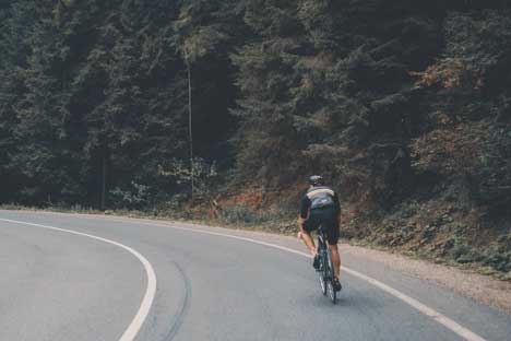 A man bicycling on a highway