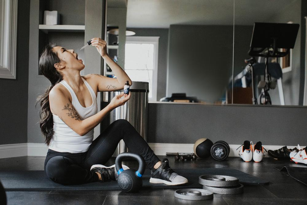 A woman taking a dropper of Energy Enhanced before a workout