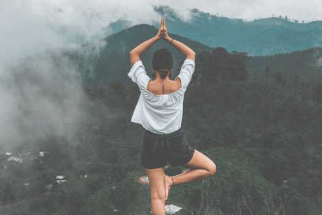 A woman practicing yoga on a mountain