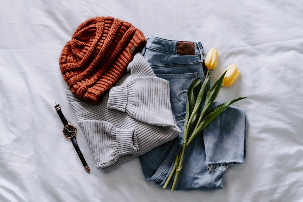 Orange knitted beanie with sweater, jeans, and tulips