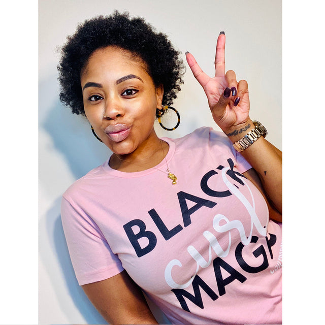 "Woman wearing shirt that reads, ""black curl magic"" makes peace sign with her fingers."