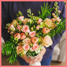 Load image into Gallery viewer, Order The Susie flower bouquet from our Mother's Day Collection.The Susie bouquet includes mixed stems of roses, coral ranunculus, stock, solomio, spray roses, and podocarpus greens. The flowers will be shipped directly from the farm to you!
