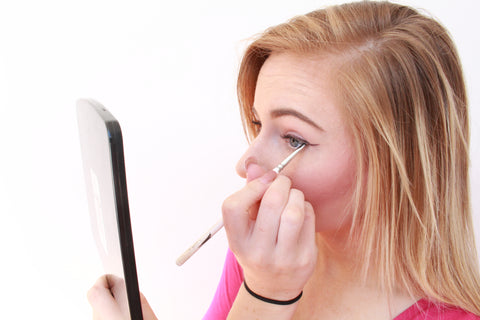 Applying eyeshadow over gel eyeliner to created a colored winged eyeliner