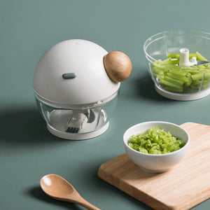 Pisu Manual Mincer next to minced vegetables on a chopping board