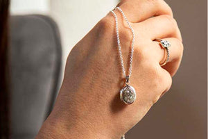 silver photo locket displayed on back of model's hand