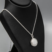 Load image into Gallery viewer, Angled view of round silver photo locket and silver chain