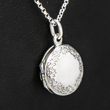 Load image into Gallery viewer, Close up view of round silver photo locket and silver chain