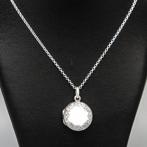 Front on view of round silver photo locket and silver chain