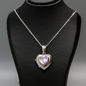 Silver heart shaped photo locket with pink mother of pearl inset with a silver Italian chain displayed on a black bust.