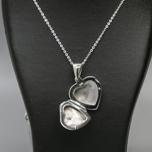 Silver heart shaped photo locket with pink mother of pearl inset with a silver Italian chain displayed on a black bust. Locket is open showing where photo is to be inserted.