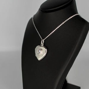 Heart-shaped photo locket necklace with cubic zirconia inset on a silver chain.