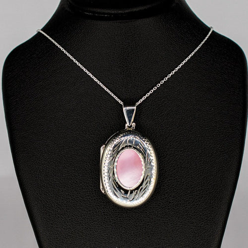 silver locket oval shaped with pink mother of pearl inset on a silver chain