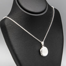 Load image into Gallery viewer, Small Oval shaped photo locket on silver chain displayed on black bust