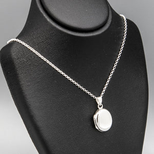 Small Oval shaped photo locket necklace on silver chain displayed on black bust