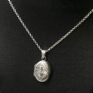 Embellished silver photo locket with lily motif on italian silver chain displayed on black bust.