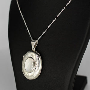 Oval shaped embellished silver photo locket necklace with white mother of pearl inlay on Italian silver chain displayed on black bust.