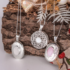 Oval shaped embellished silver photo locket necklace with white mother of pearl inlay on Italian silver chain and a round photo locket necklace and an oval with pink photo locket necklace on a Christmas log.