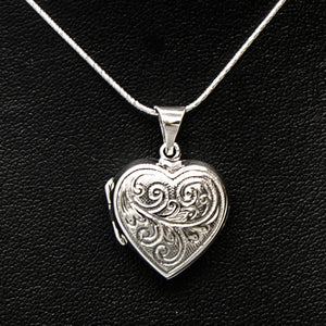 Silver shaped photo locket with embellishment on silver chain displayed on black